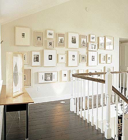 gallery wall of family photos with neutral mats.