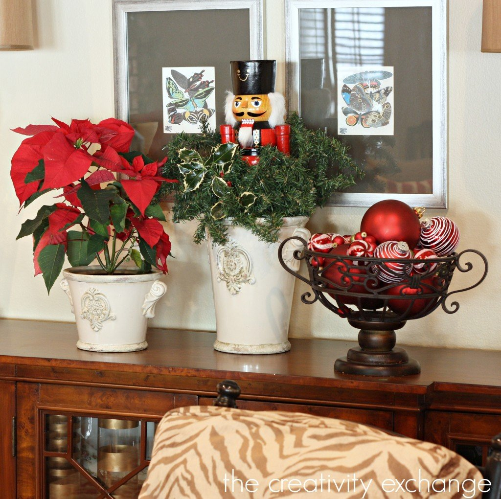 Nutcracker coming out of urn mixed with holly and garland. {The Creativity Exchange}