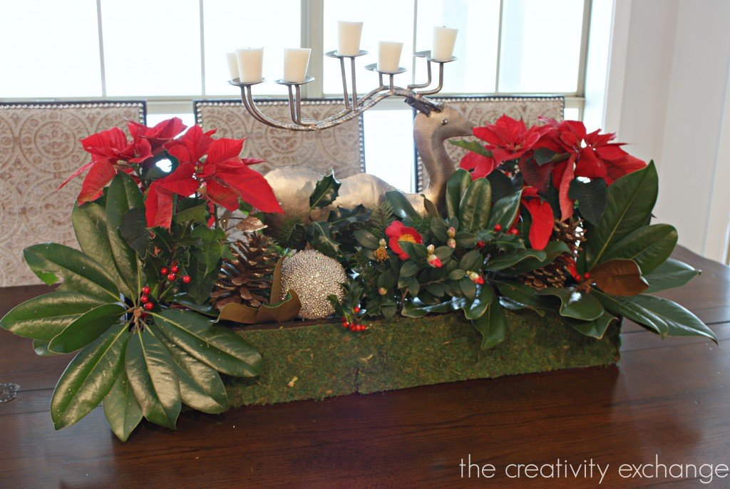 Reindeer candle holder in wooden box filled with poinsettias and magnolias. The Creativity Exchange