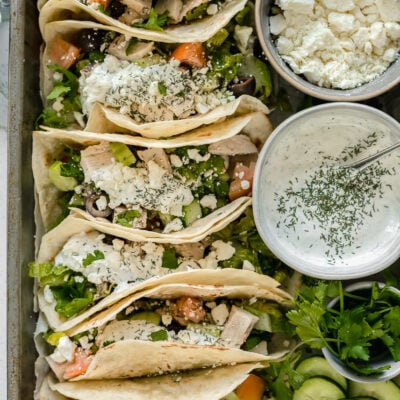 An overview shot of greek tacos with a cucumber dill sauce