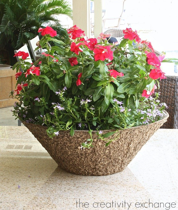 Fill an oversized low bowl planter with a hanging mixed plant basket for a gorgeous outdoor table arrangement. The Creativity Exchange.