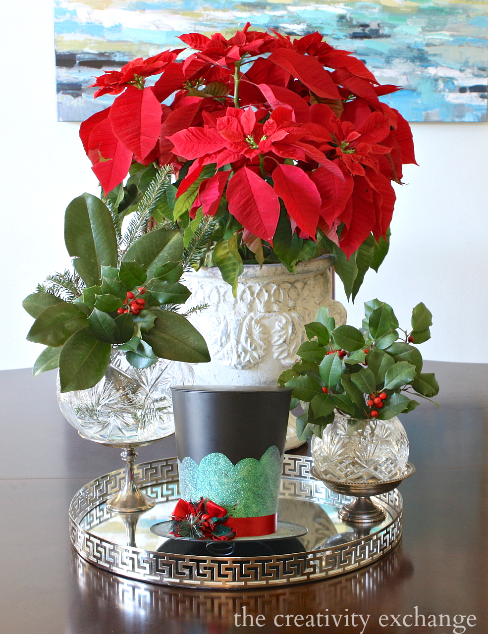 Christmas Centerpiece using fresh holly, pointsettia and top hat tree topper. The Creativity Exchange Christmas Home Tour