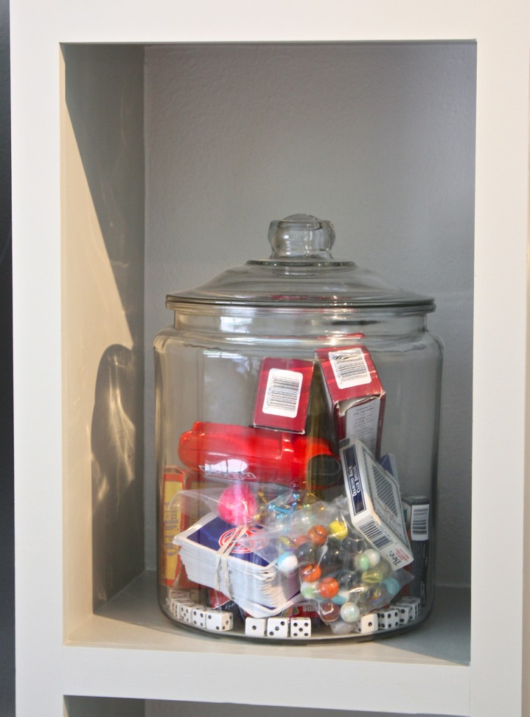 Use oversized glass cookie jars for organizing small games, cards and little game pieces in family room.
