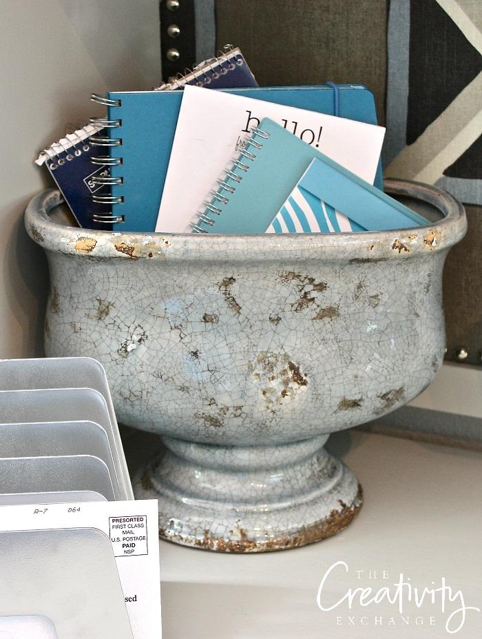 Use garden urns for storing notebooks and calendars on desk.