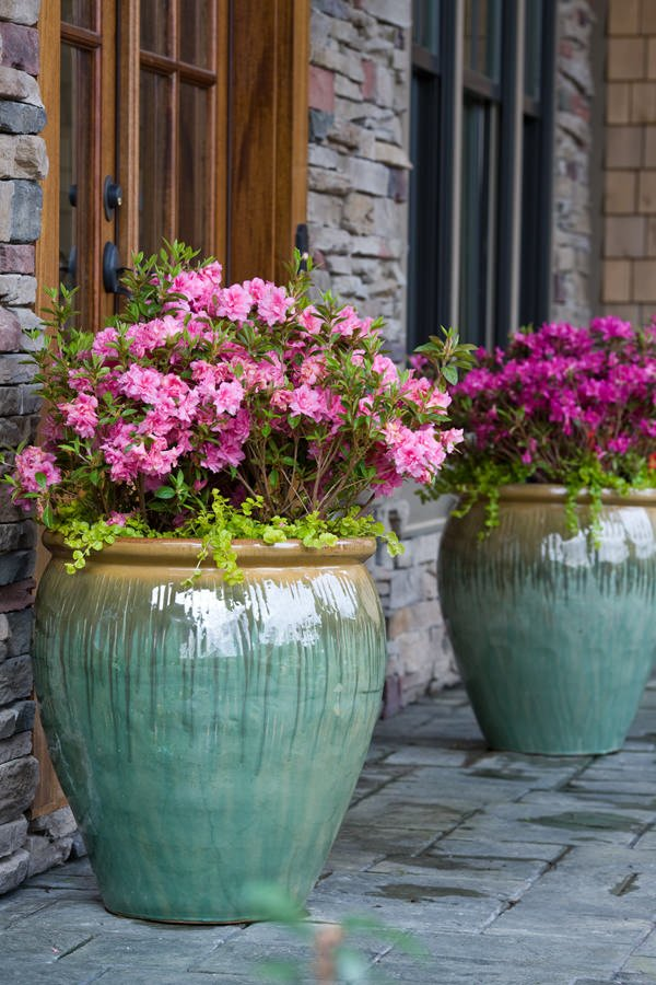 Fill glazed pots and urns with empty plastic planters and rest flowers and plants in the top.