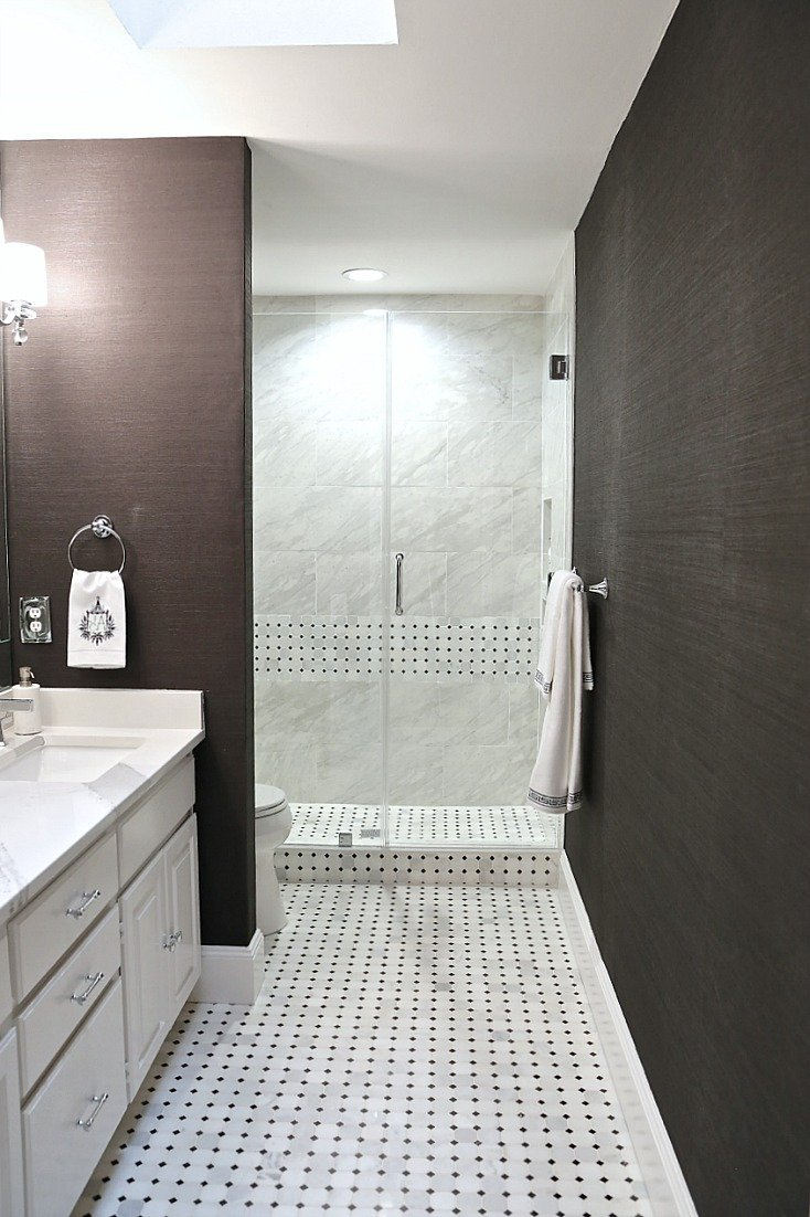 Black grasscloth wallpaper and marble mosaic tiles
