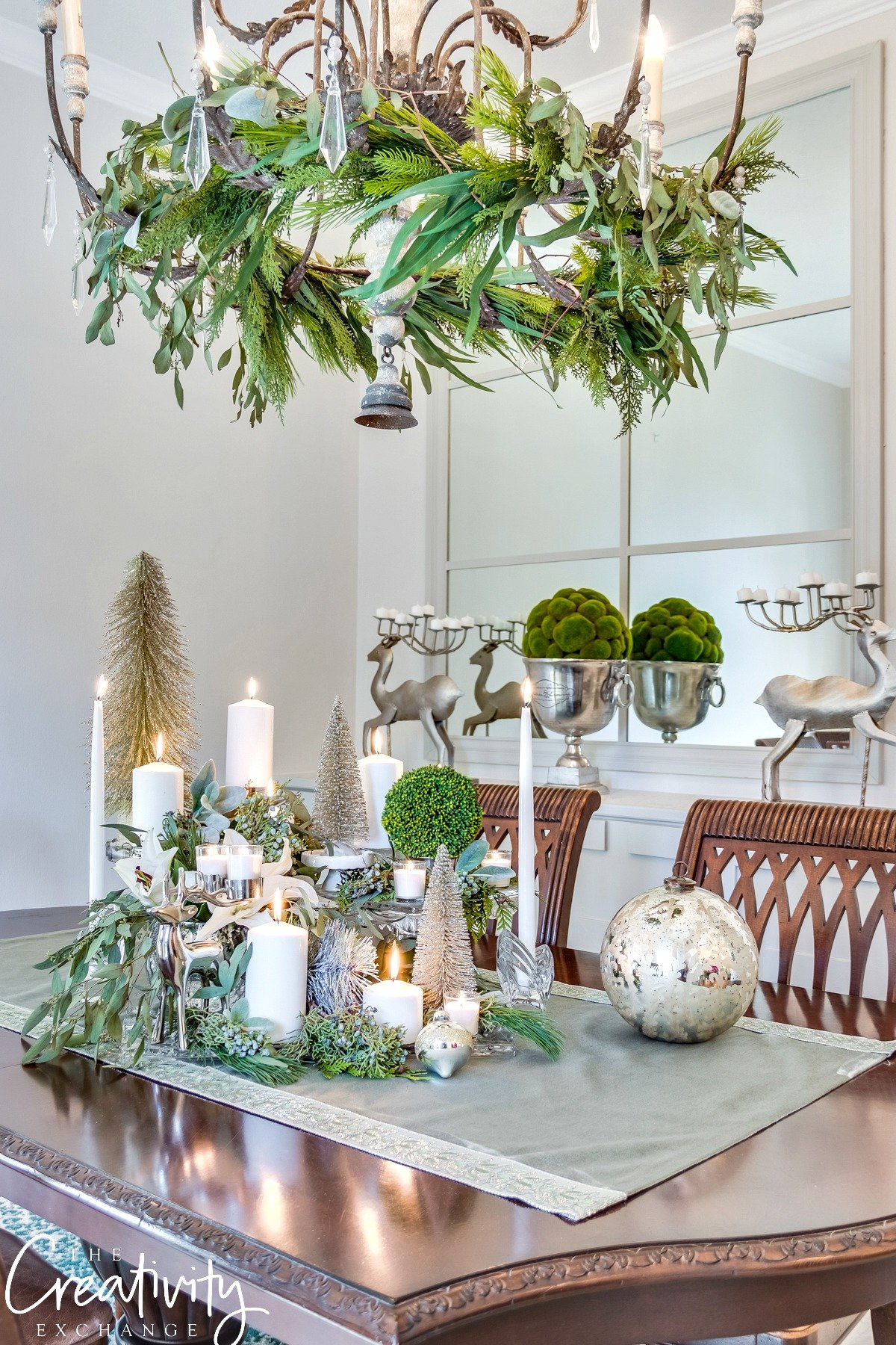 Christmas tablescape with layered cake stands and greenery.