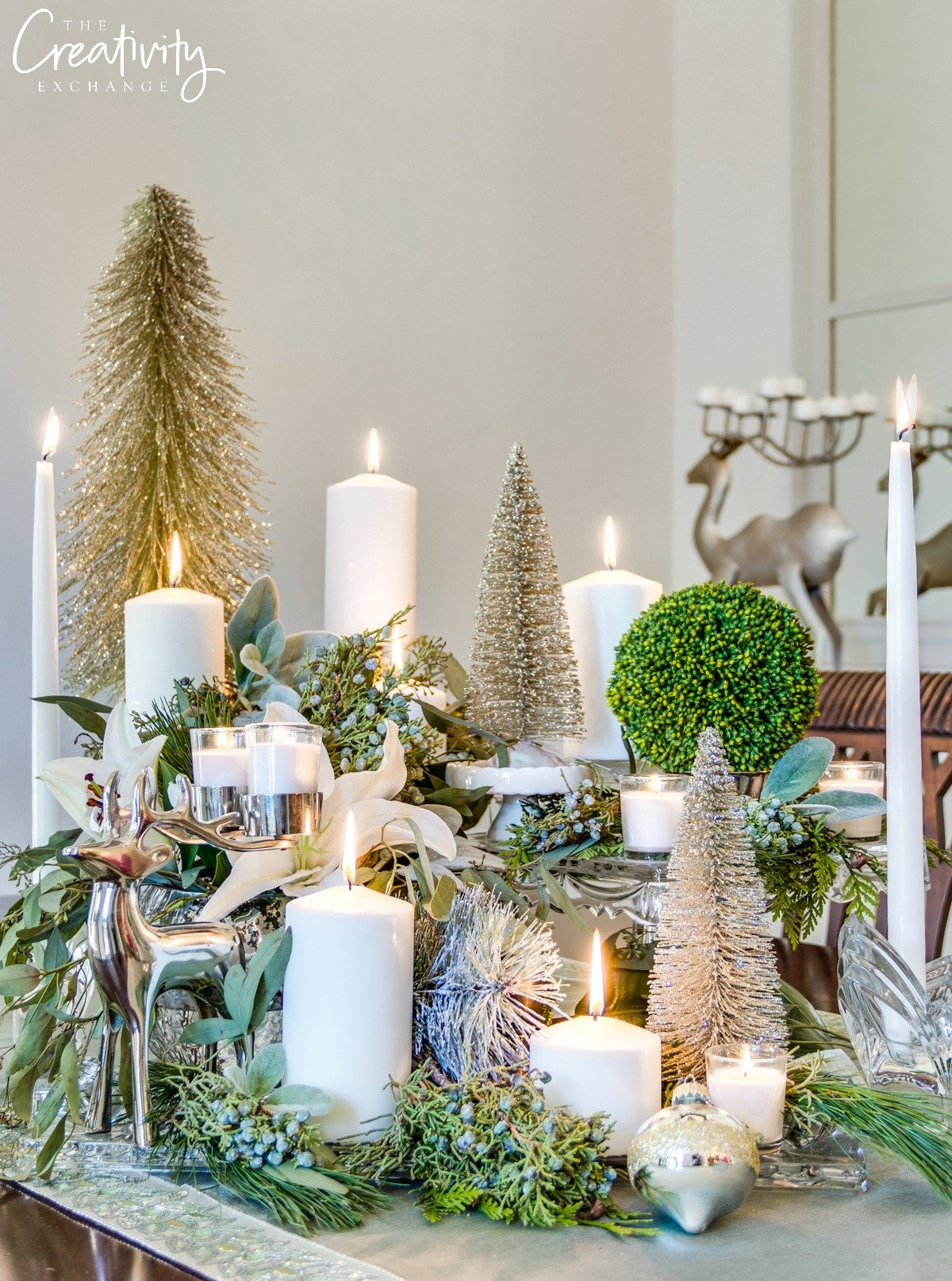 Christmas tablescape using layered cake stands, greenery and candles.