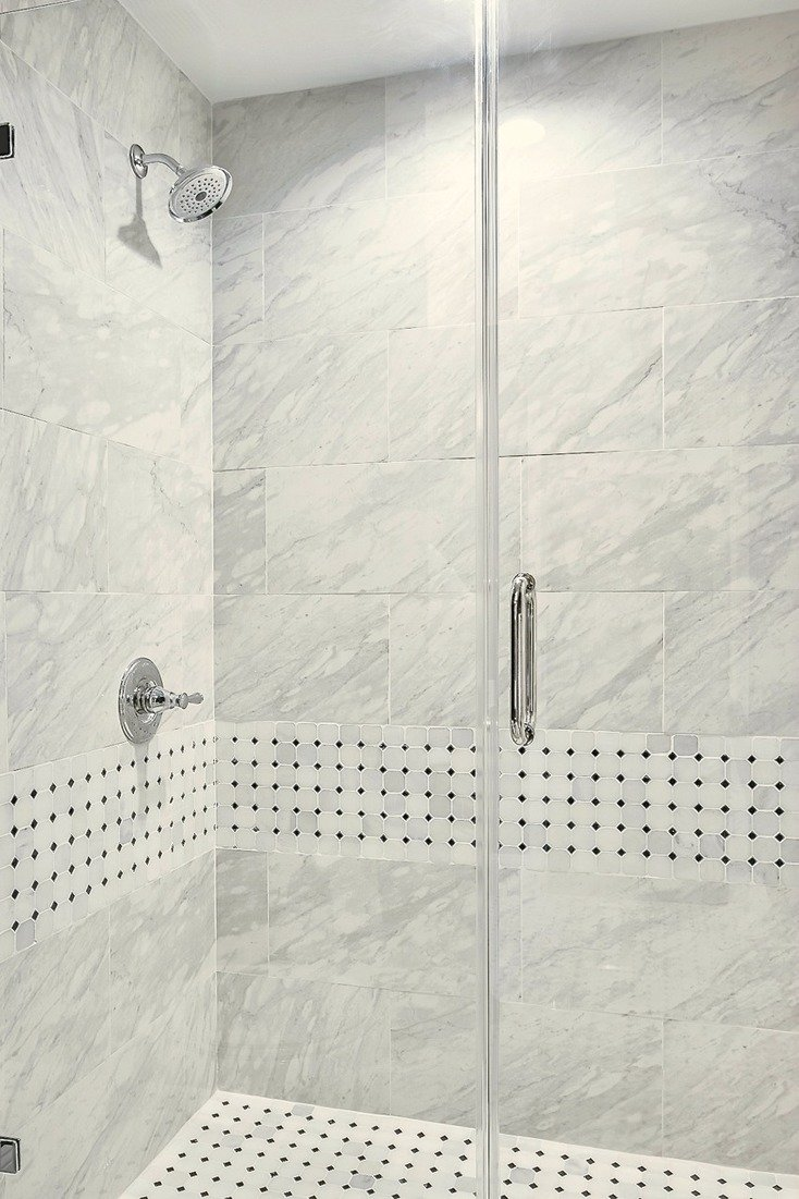 Frameless glass walk in shower with Delta Silverton Fixtures. Porcelain marble alternative tile.