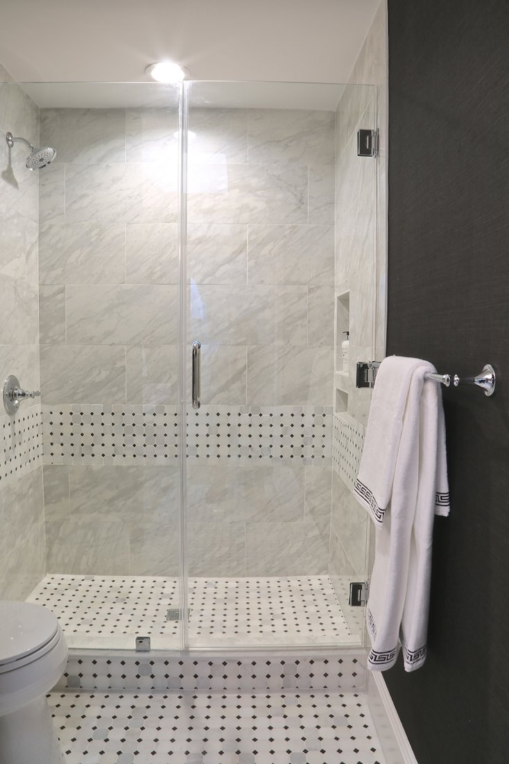frameless-glass-walk-in-shower-with-delta-silverton-fixtures-porcelain-marble-alternative-tile