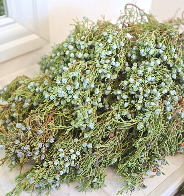 Fresh juniper berries and branches worked into Christmas garlands and wreaths.