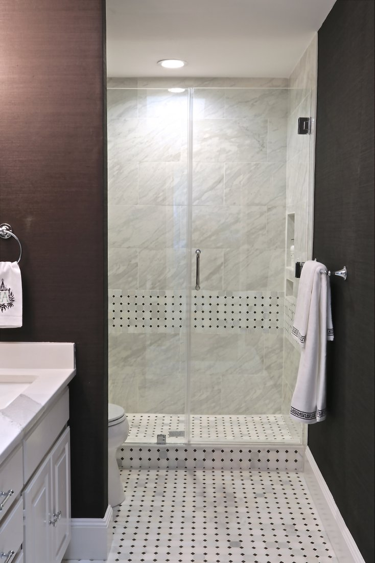 Walk in shower with framelss glass doors. Marble mosaic tile and porcelain wall tile