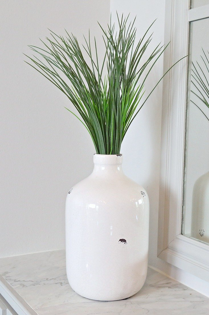 Artificial wheat grass in jug.