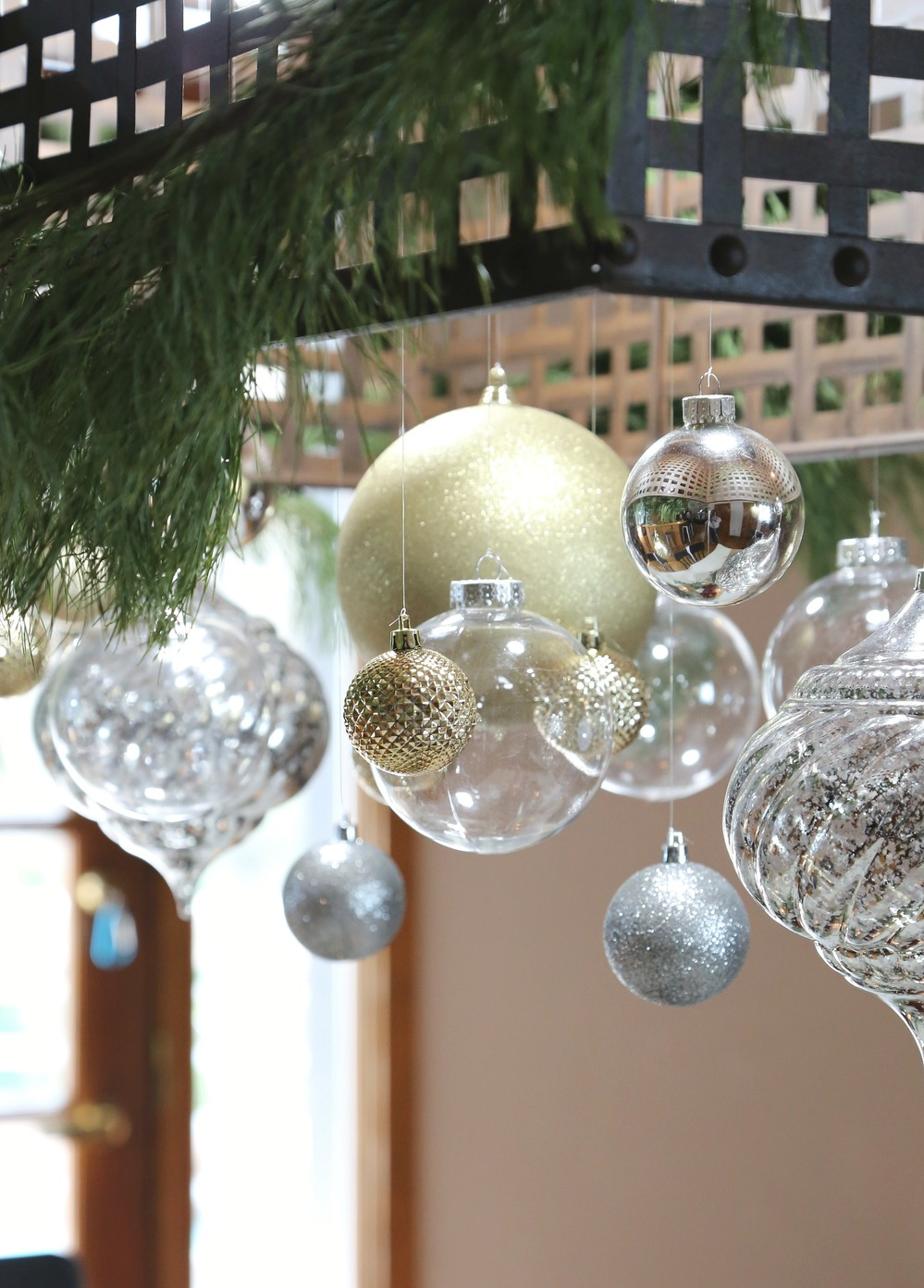 Christmas ornaments hanging from light fixture.