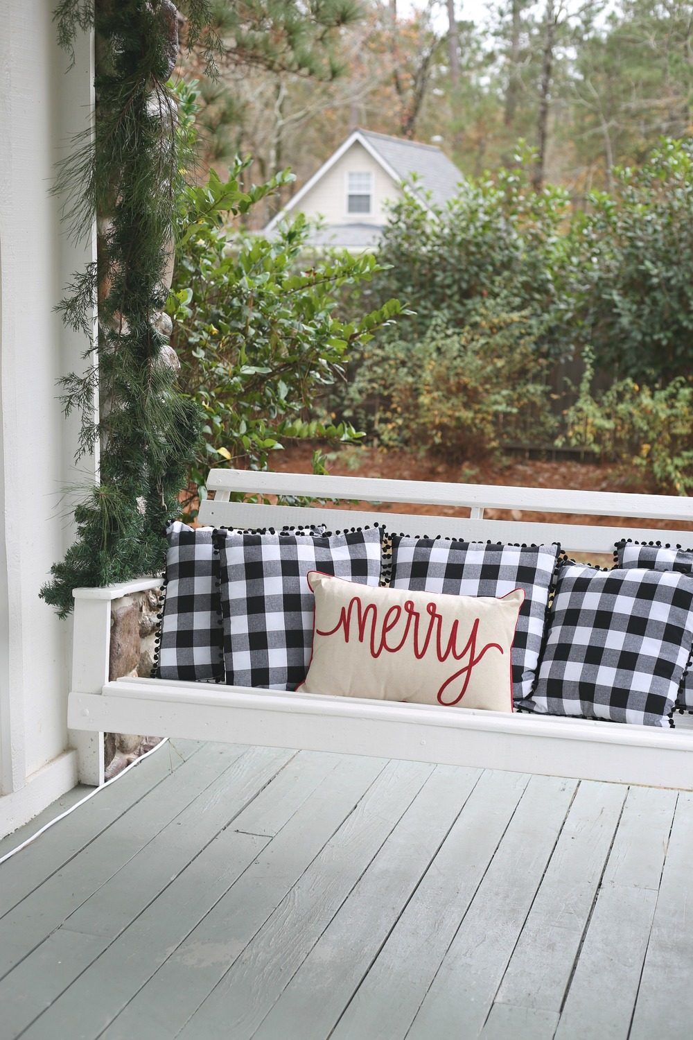 Christmas porch swing covered in garland