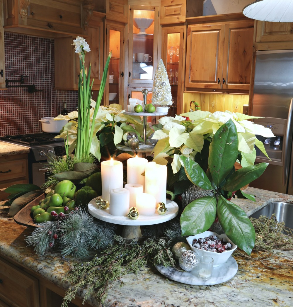 Kitchen counter Christmas arrangement with candles and fresh greenery.