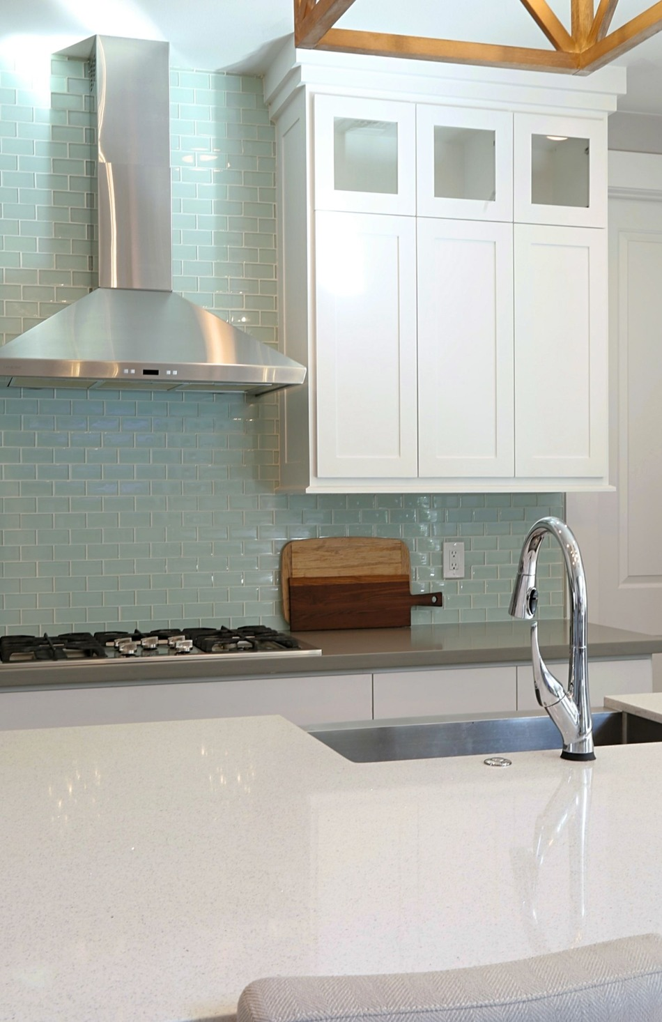 White kitchen with blue green subway tile and Delta Faucet.