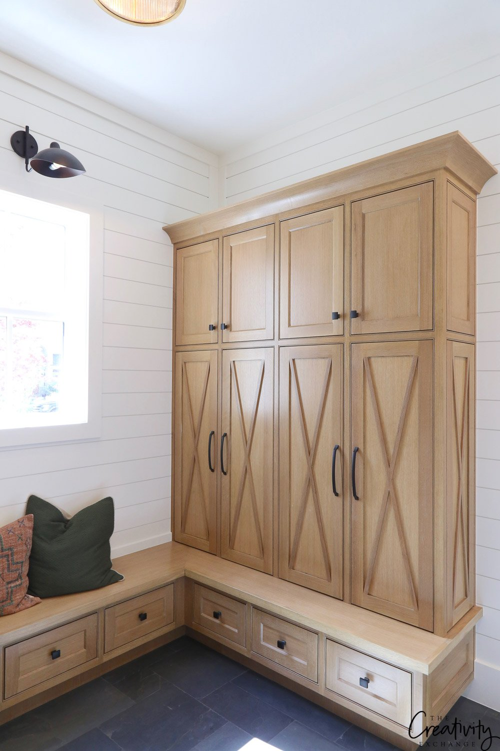 Modern farmhouse mudroom with enclosed natural wood cabinets.
