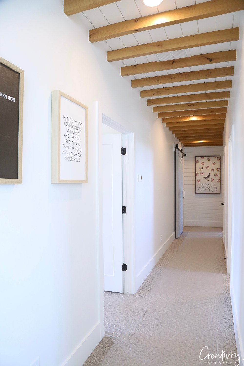 Long narrow hallway with natural wood ceiling beams