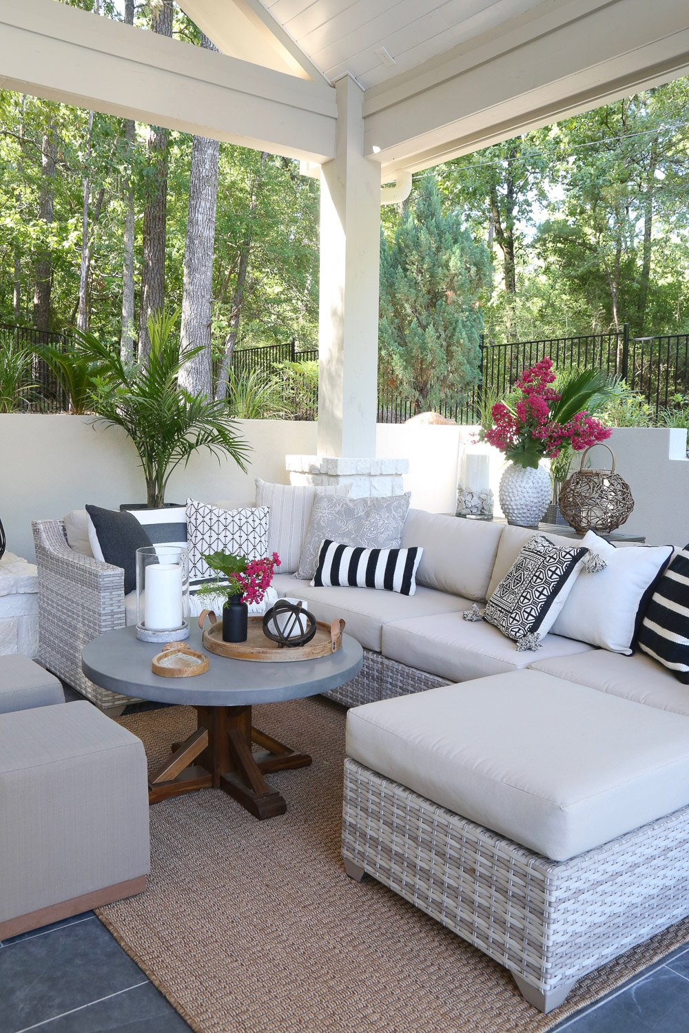 Outdoor patio with plants and pillows.
