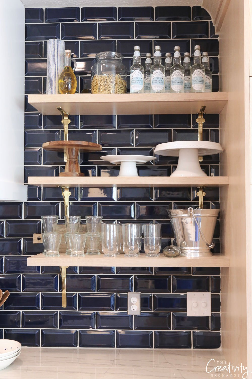 Navy kitchen tile backsplash and open shelving.