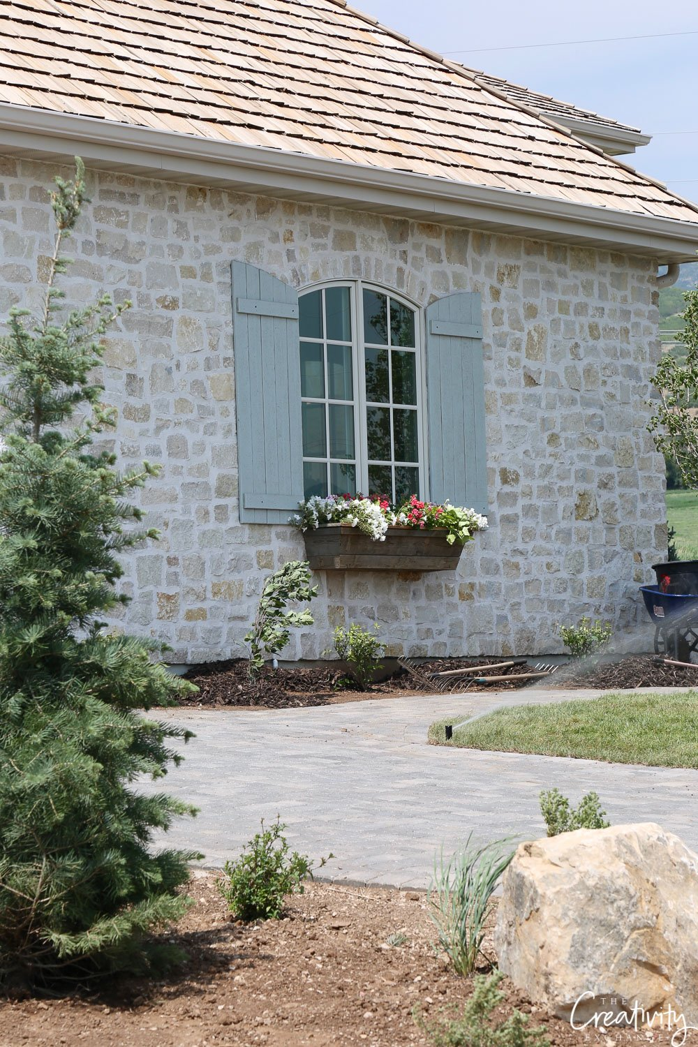 Stone home with blue shutters and window box.