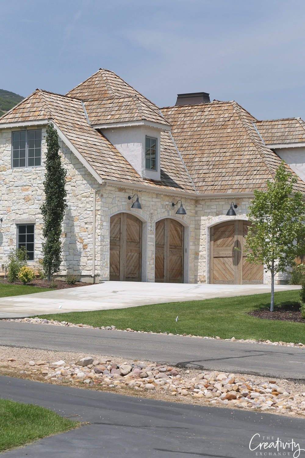 Stone exterior home with reclaimed wood garages.