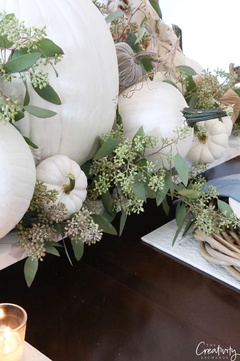 White pumpkins mixed with seeded eucalyptus