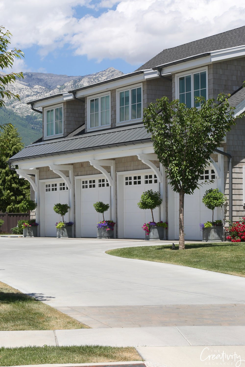 Four car garage with shaker exterior design.