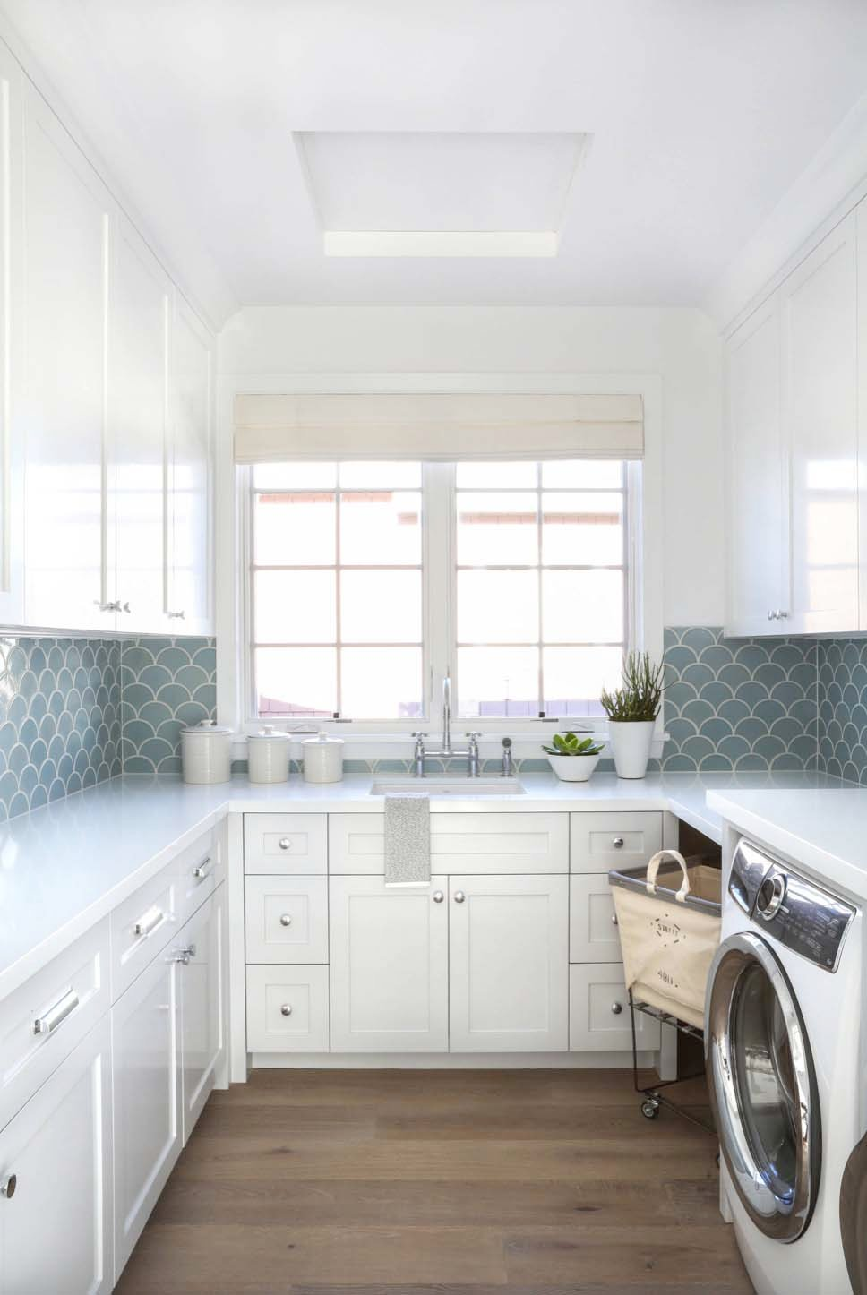 Blue tile backsplash in laundry room. Brandon Architects