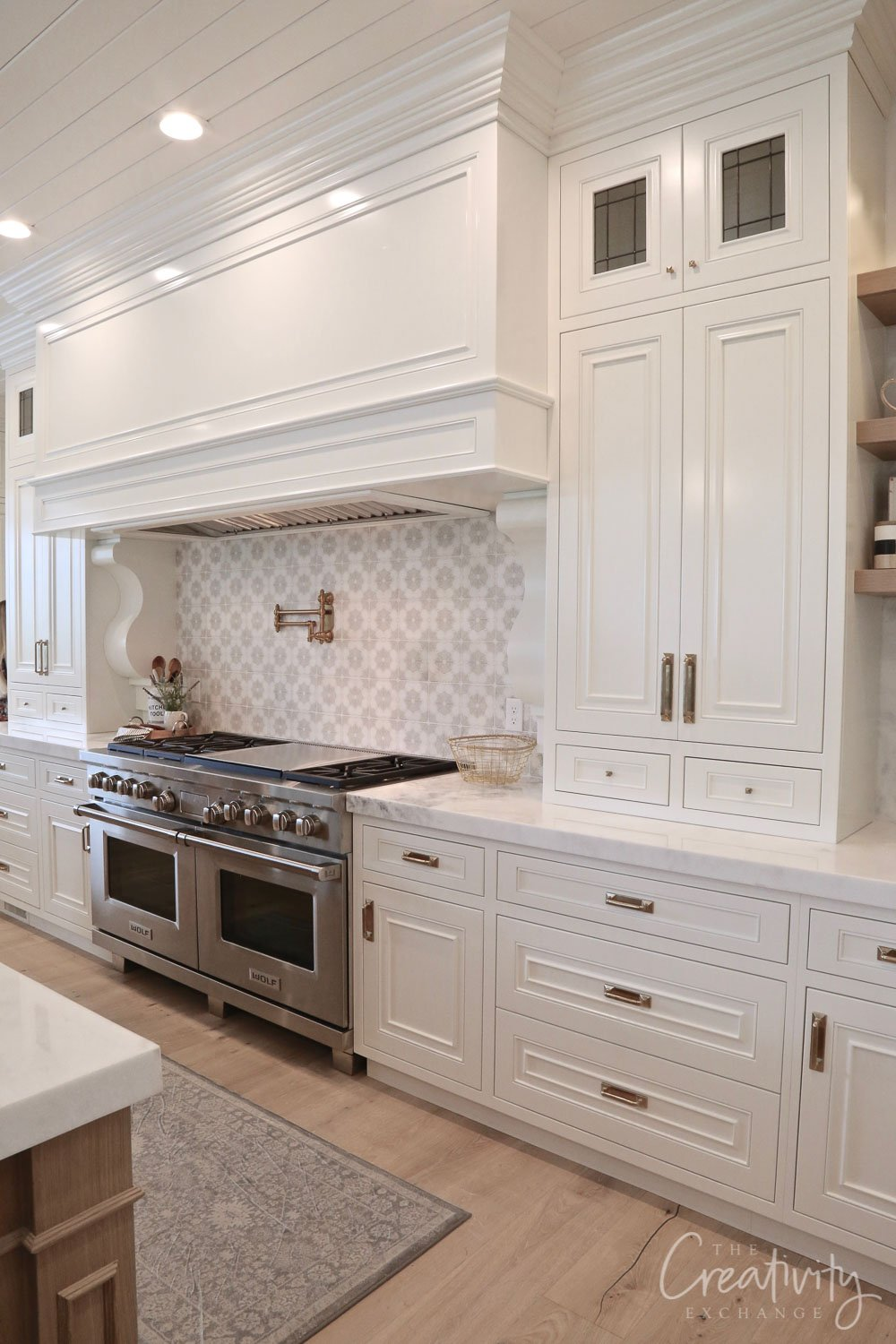 White kitchen with large vent hood