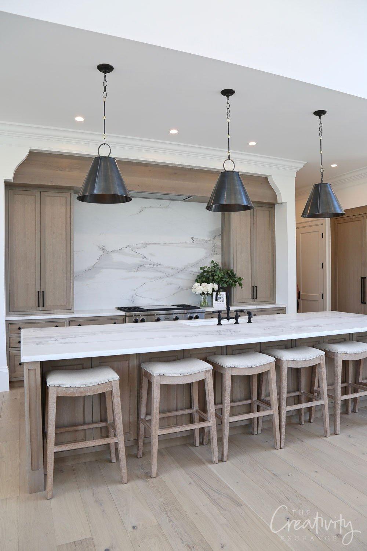 Kitchen with natural wood and marble slab backsplash