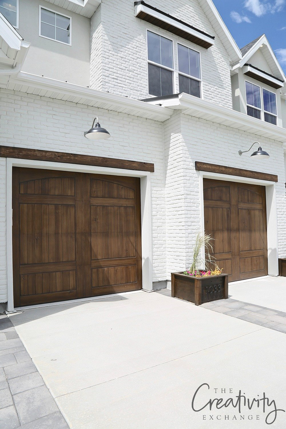 Painted brick exterior with natural wood trim accents and garage doors.
