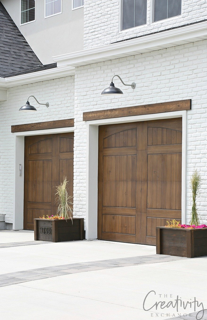 Painted exterior brick with wood trim accents and garage doors.
