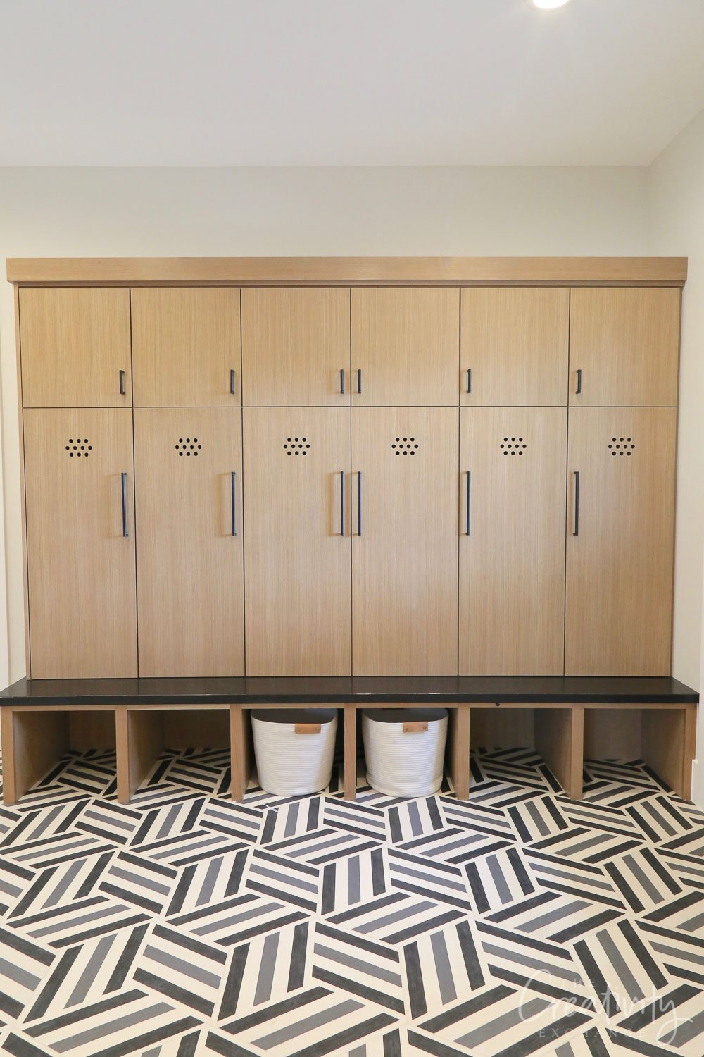 Mudroom with oak storage lockers and cement tile