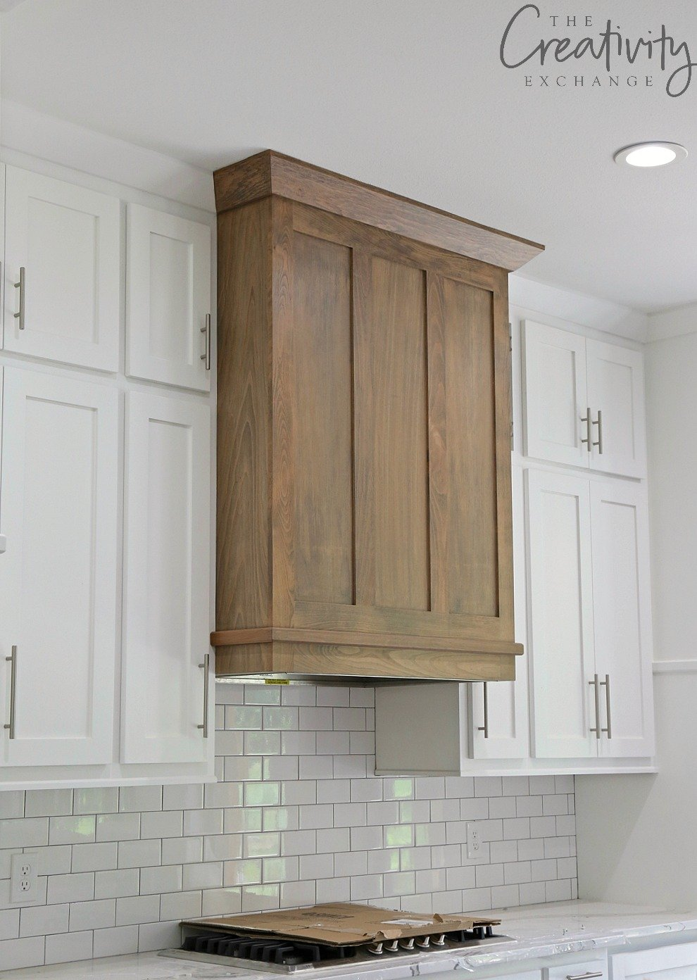 Custom wood vent hood mixed with white cabinets