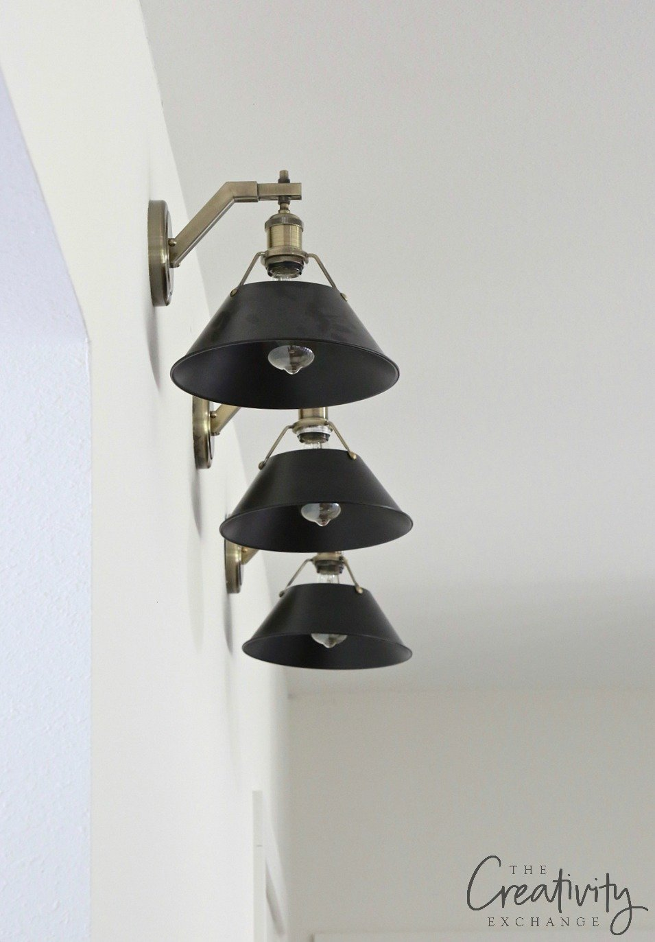 black and brass sconces for gallery wall