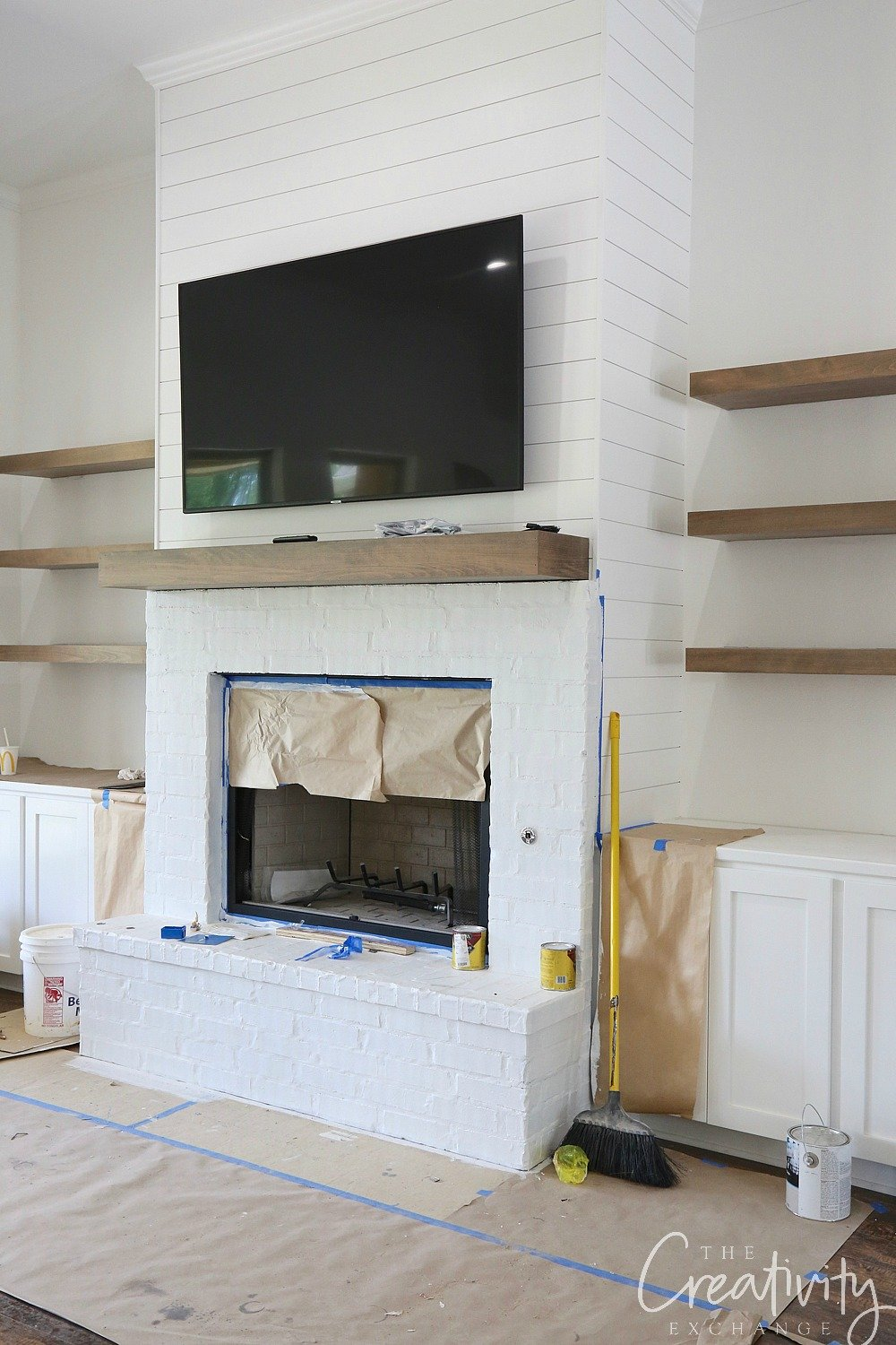 white shiplapped fireplace with oak floating shelves