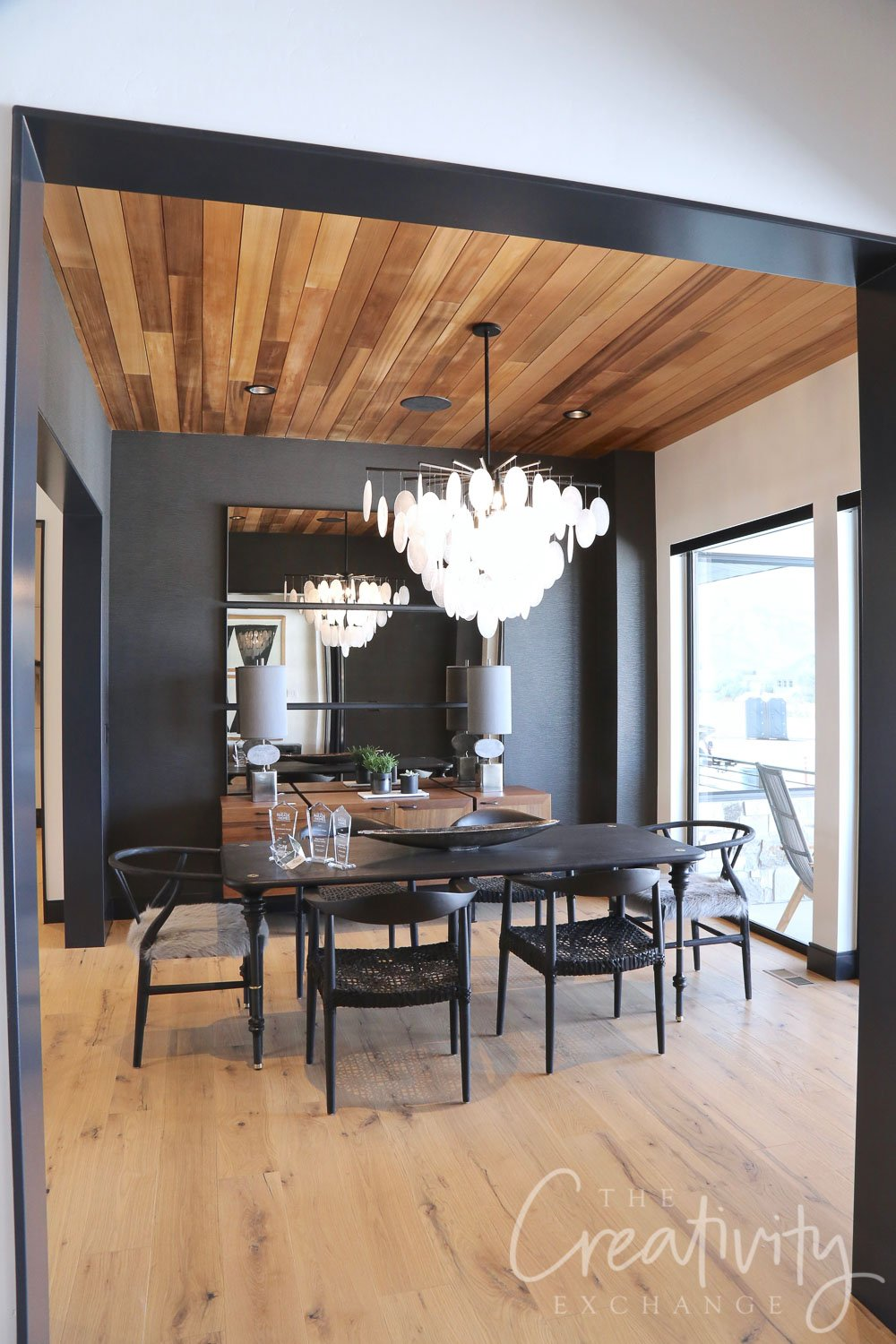Black dining room accent wall with wood ceiling.