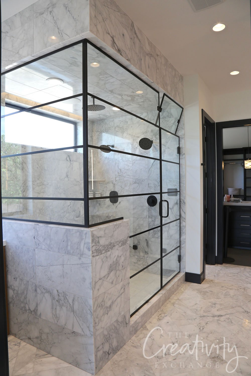 Large marble shower with black industrial shower door and glass