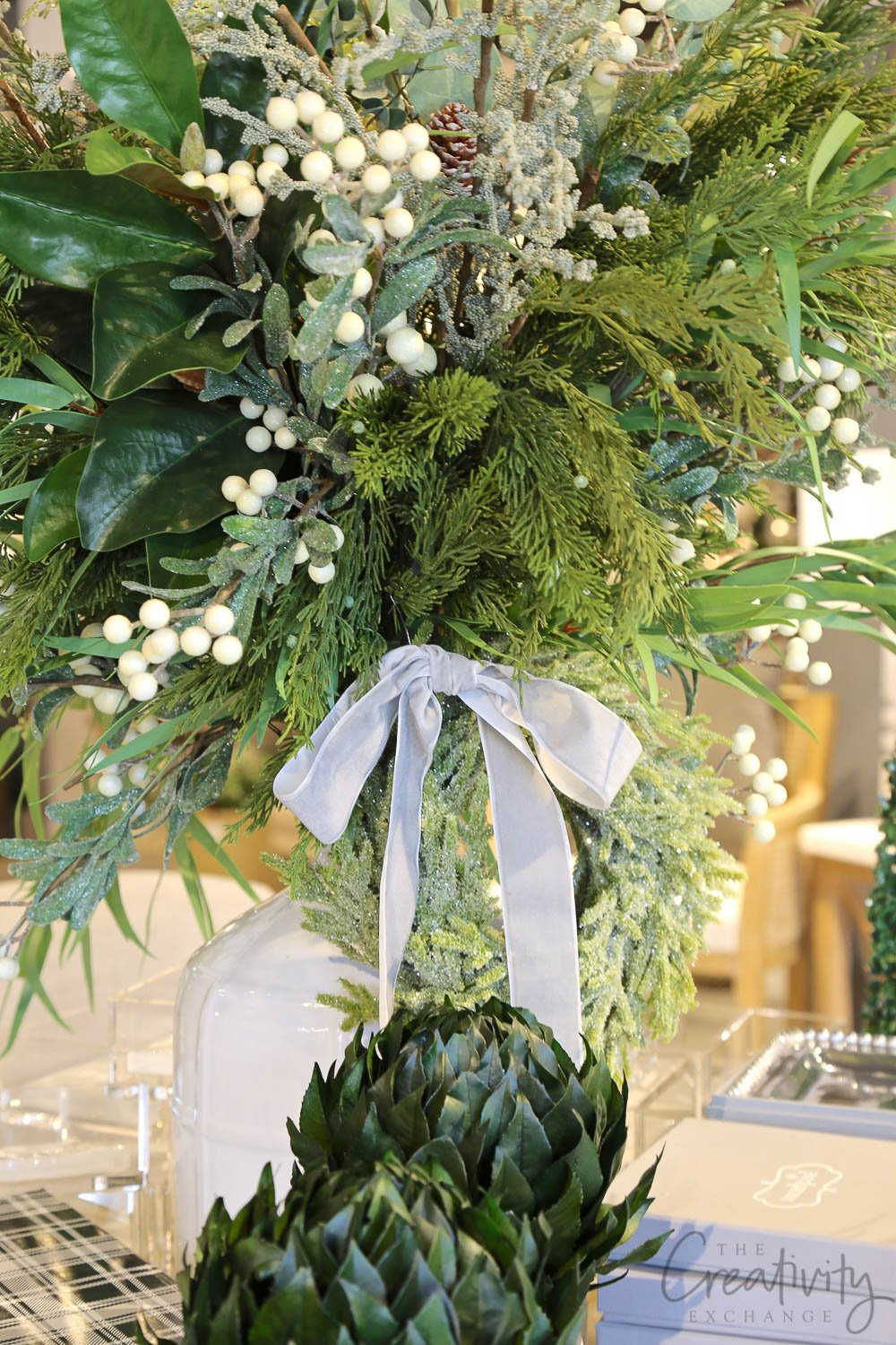 Christmas greenery in a tall white jug