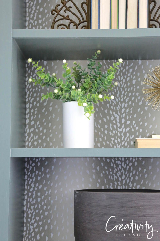 Bookshelves with antelope wallpaper