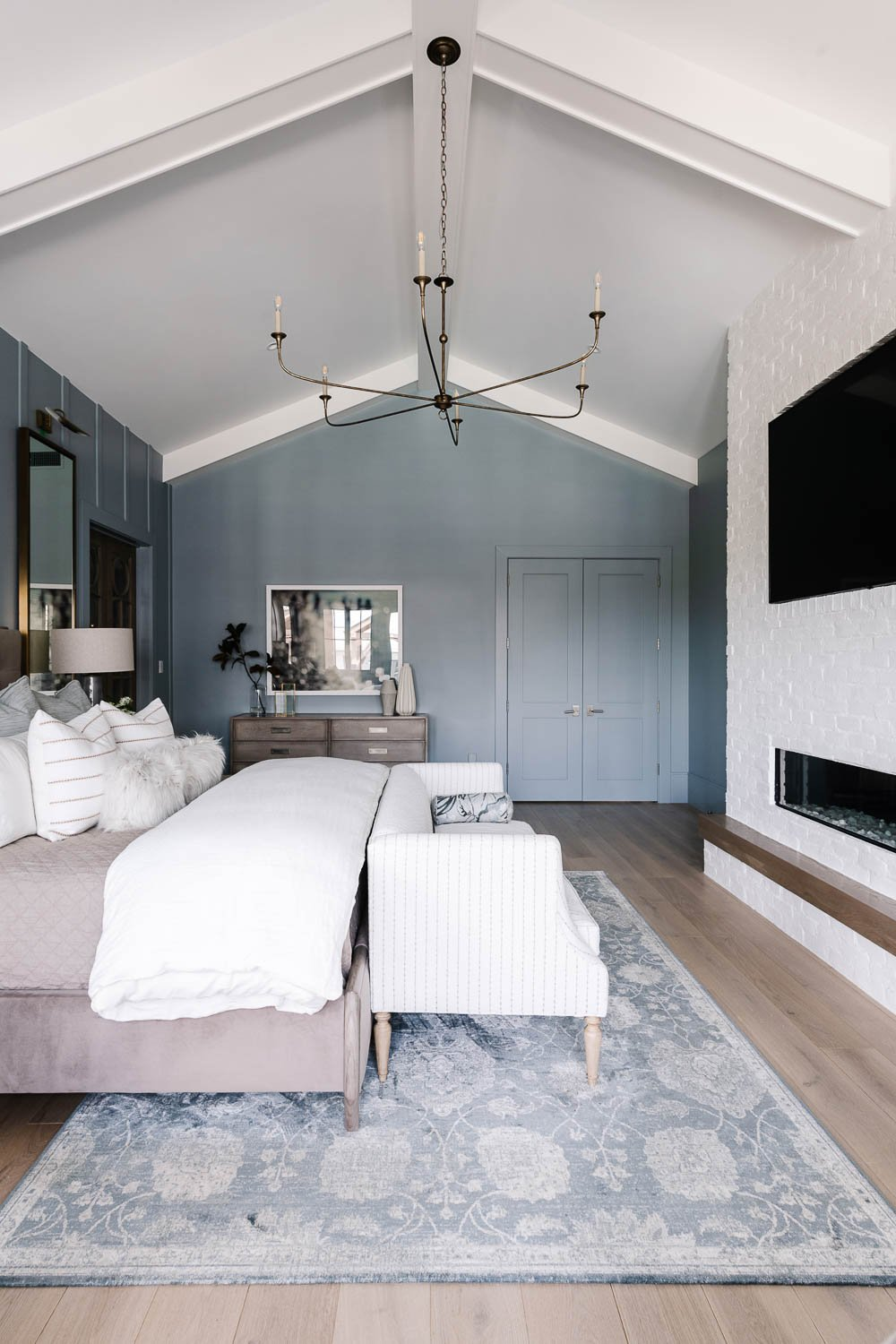 Soft blue painted primary bedroom walls