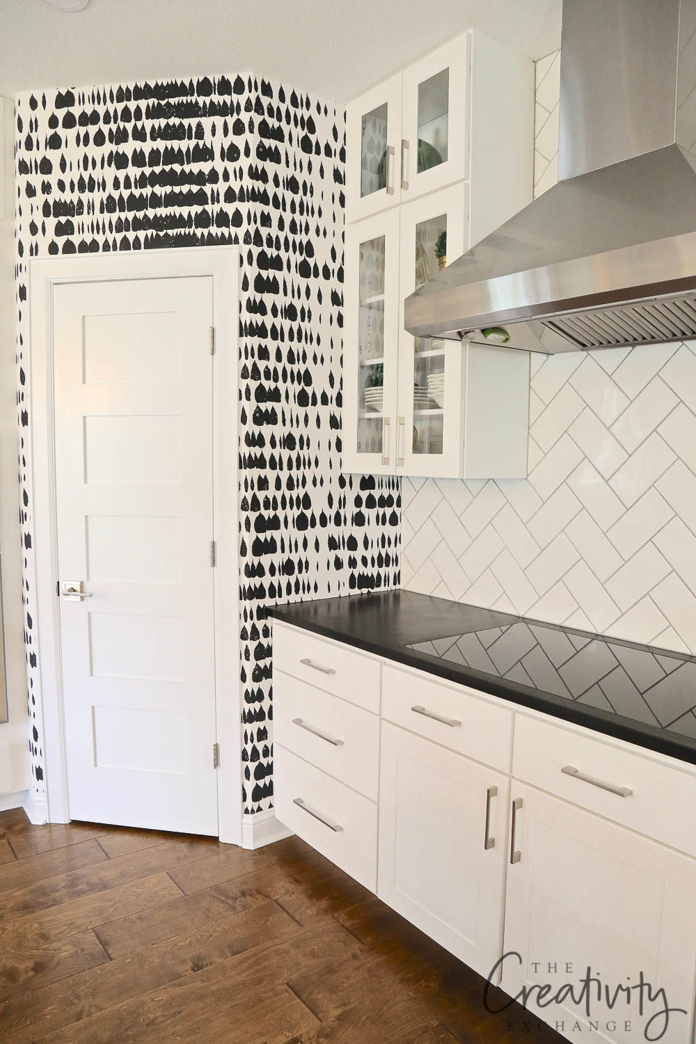 Kitchen with subway on herringbone and wallpaper