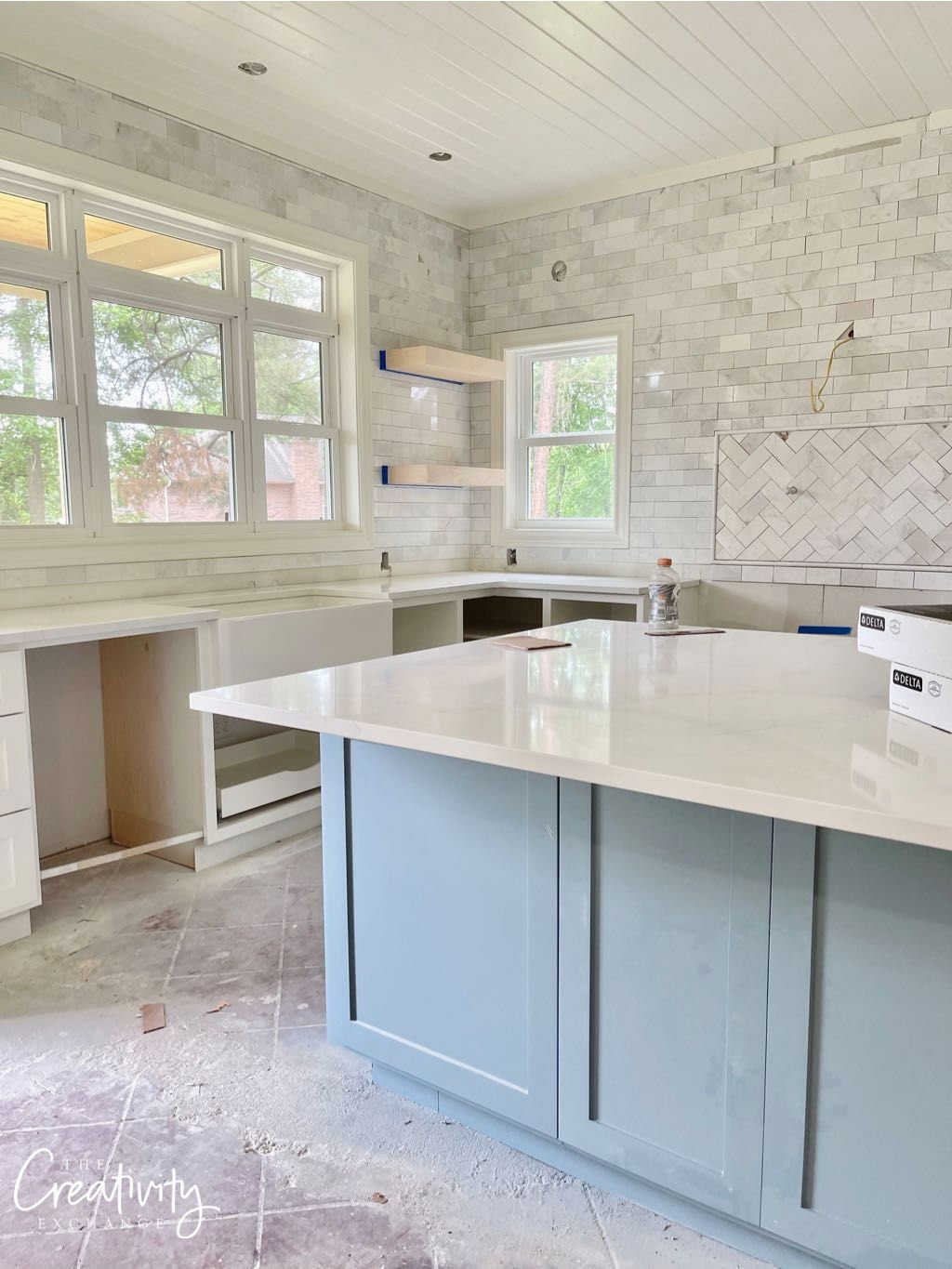 Blue painted kitchen island with marble subway tile