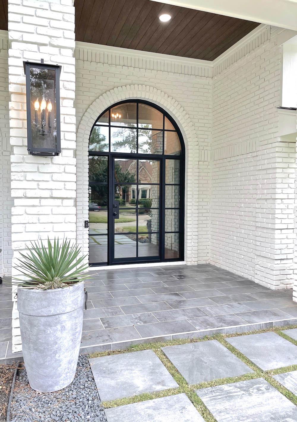 Large arched modern steel grid front door