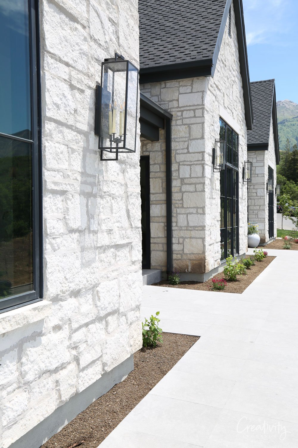 Limestone home exterior mixed with black windows