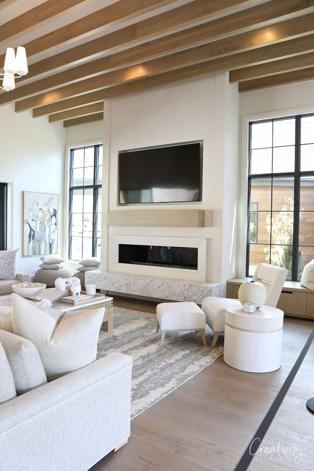 Large open living room with wood beams on ceiling